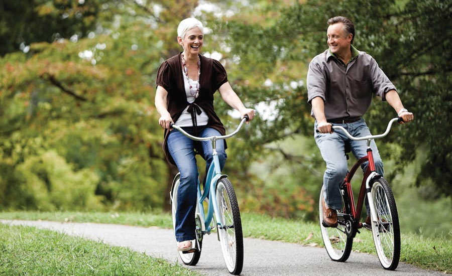 A Woman And Man Riding Bicycles Next to Each Other