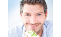 Man Smiling While Eating Healthy Snack