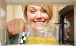 Woman Looking at Pouch in Microwave