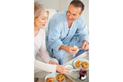 man and woman eating muffins