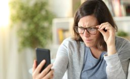 Woman Wearing Glasses While Looking at Phone