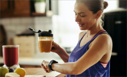 Woman Looking at Watch and Holding Smoothie